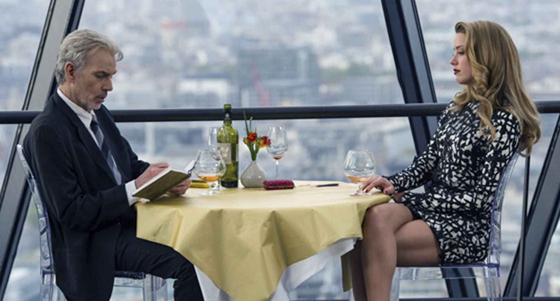 "Billy Bob Thornton (as Samson Young) and Amber Heard (as Nicola Six) sitting at a table in ""London Fields"""