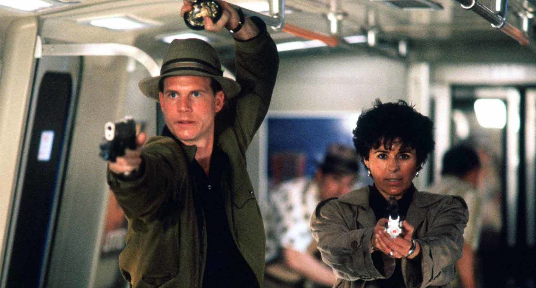 "Bill Paxton (as Jerry Lambert) and Maria Conchita Alonso (as Leona Cantrell) aiming guns in the movie ""Predator 2"""