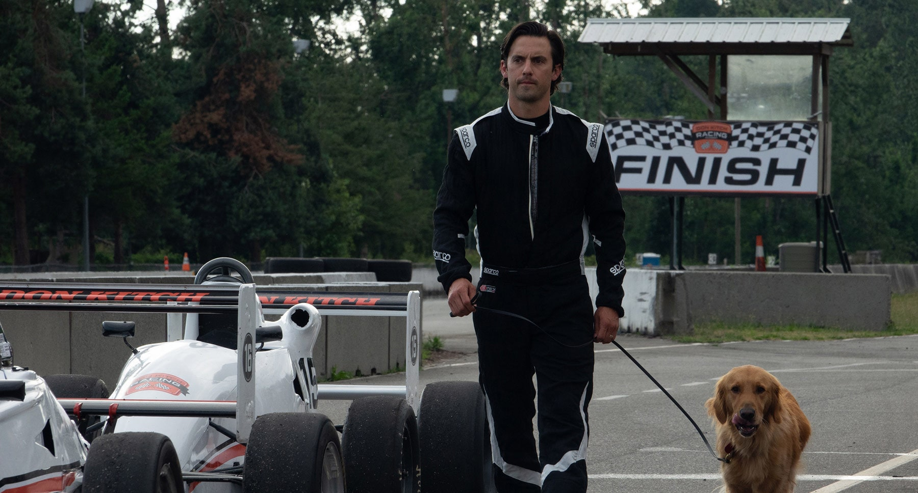 "Denny (Milo Ventimiglia) and dog Enzo at the racetrack in the movie ""The Art of Racing in the Rain"""