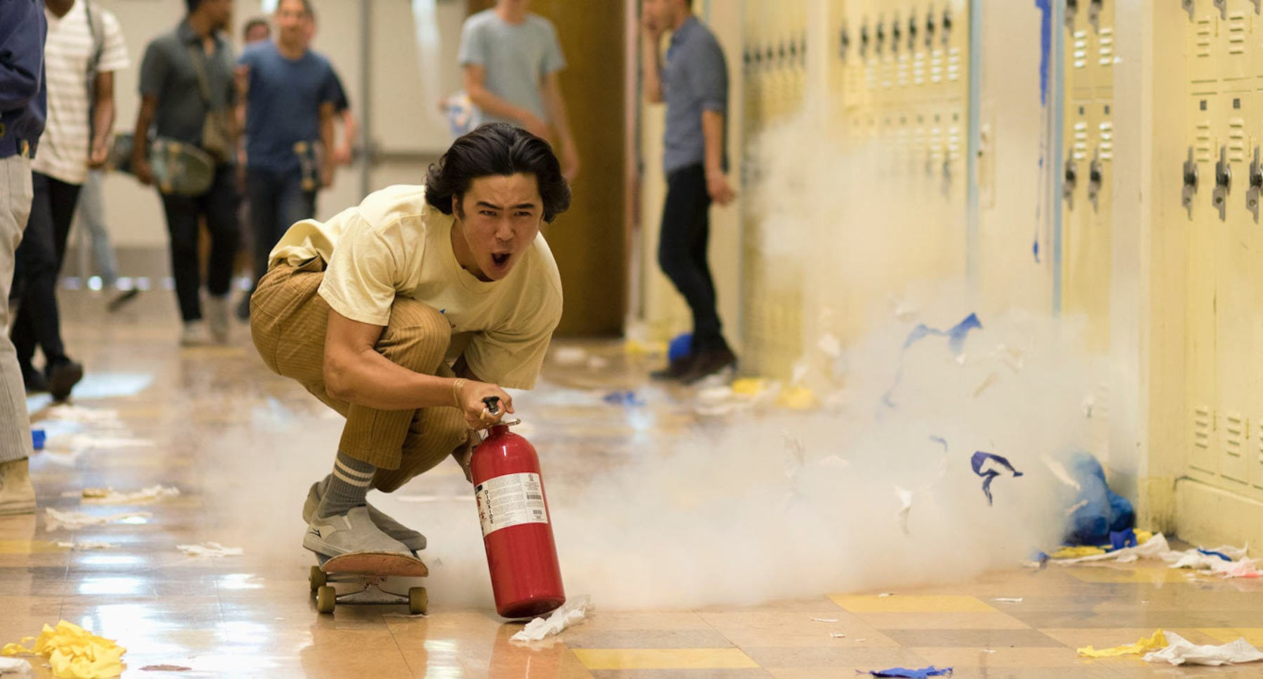 "Actor Nico Hiraga (as Tanner) riding a skateboard propelled by a fire extinguisher down a school hallway  in the movie ""Booksmart"""