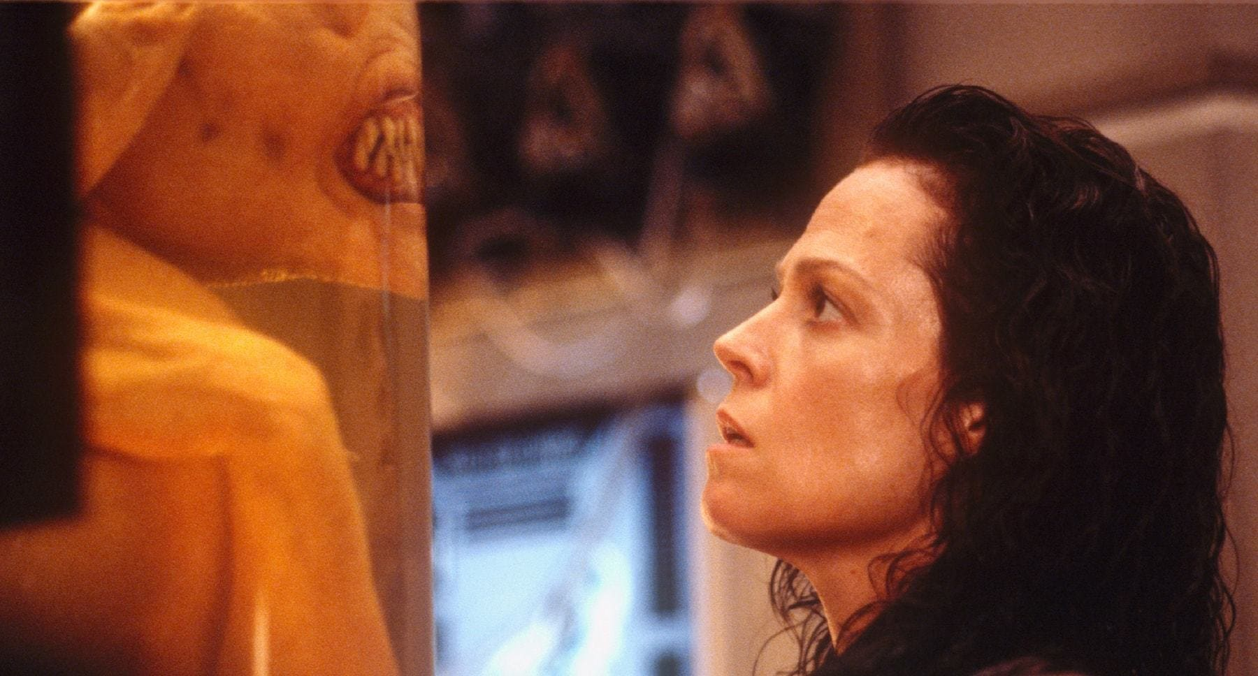"Actor Sigourney Weaver (as Ripley) staring at an alien in a tube in the film ""Alien: Resurrection"""