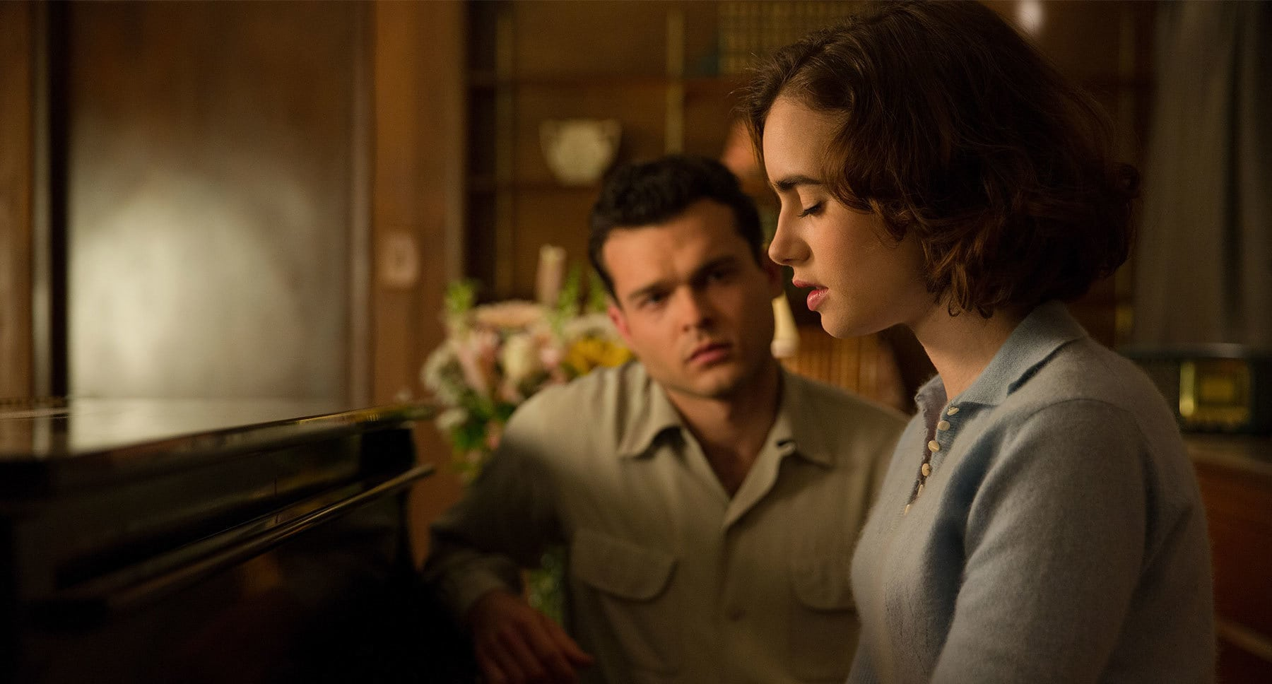 "Alden Ehrenreich (as Frank Forbes) and Lily Collins (as Marla Mabrey) sitting at a piano in ""Rules Don't Apply"""