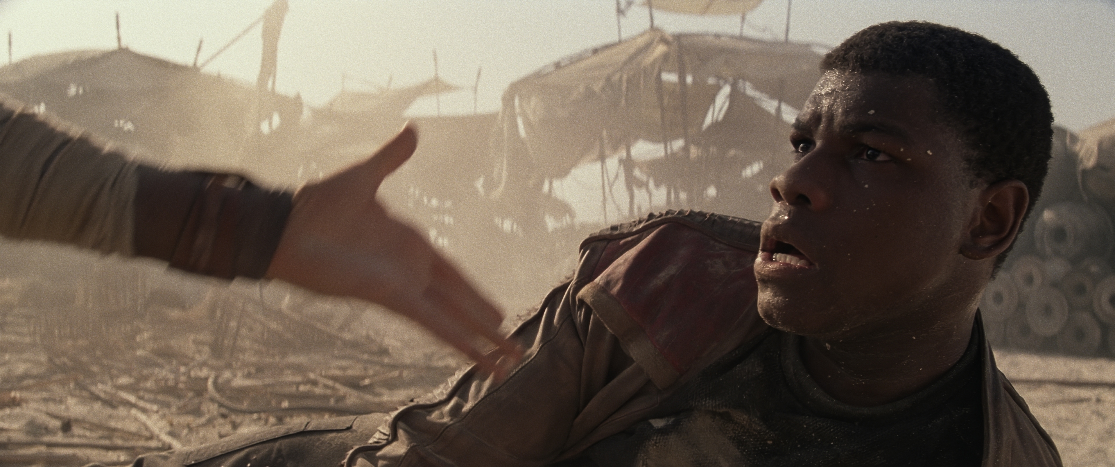 Rey played by Daisy Ridley helps Finn played by John Boyega  on Jakku.