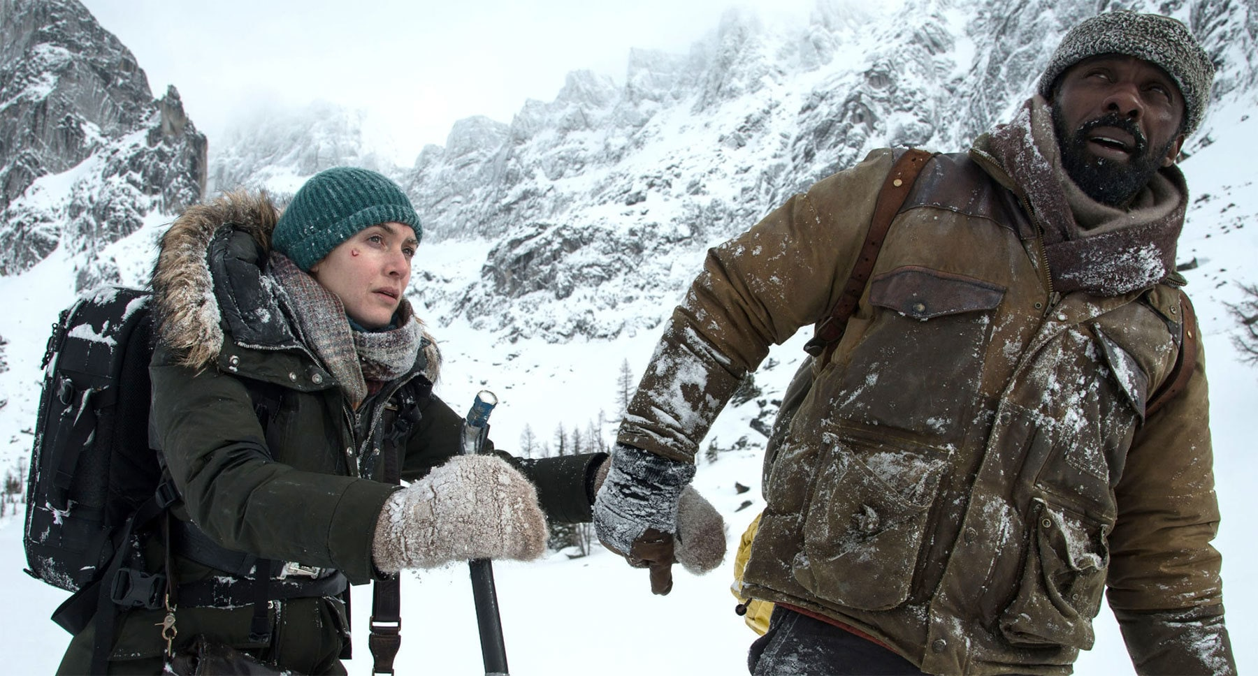 "Kate Winslet (as Alex Martin) and Idris Elba (as Ben Bass) on a snowy mountain in the movie ""The Mountain Between Us"""