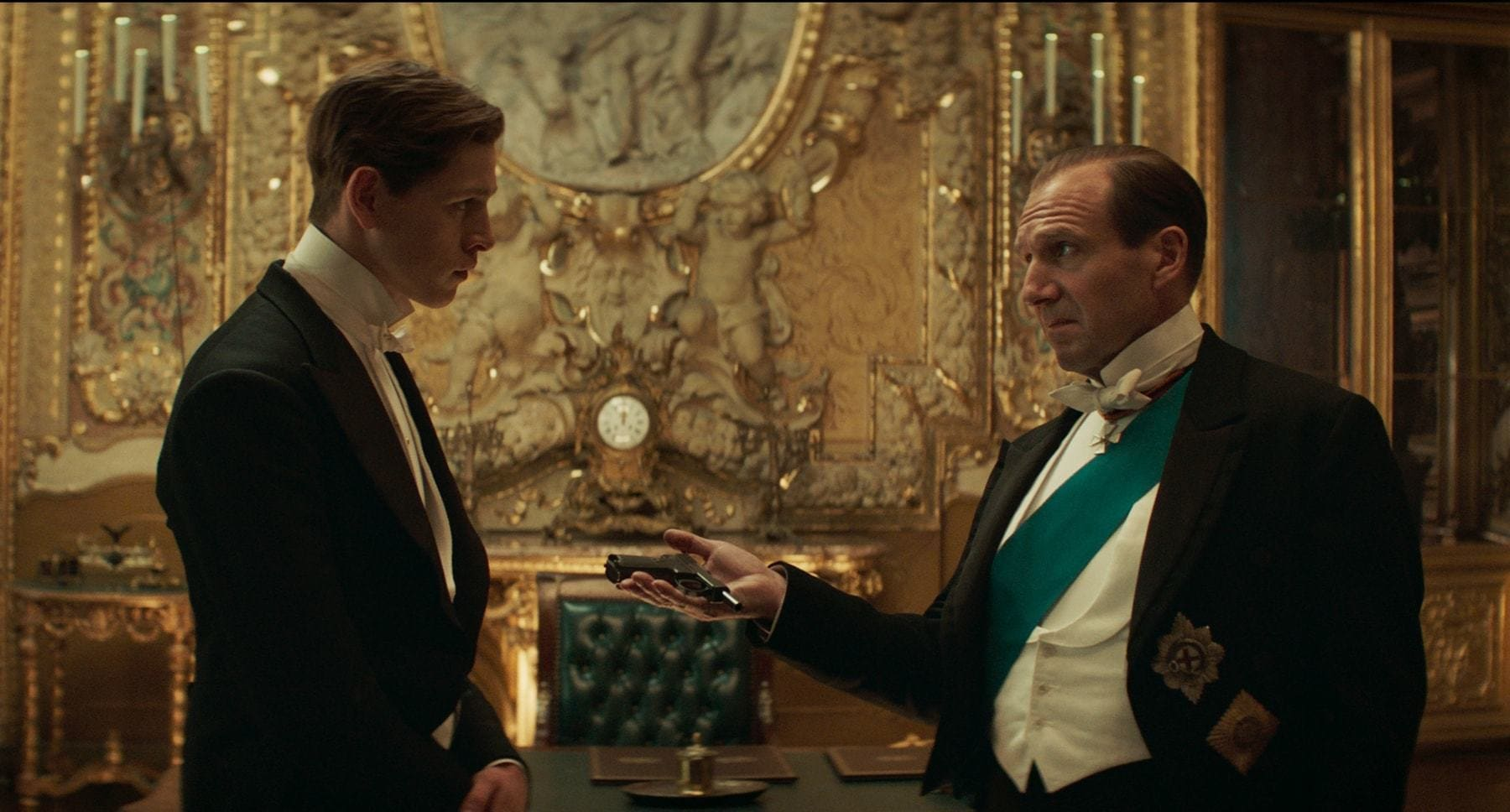 "Ralph Fiennes (as Duke of Oxford) and Harris Dickinson (as Conrad) talking to each other in the movie ""The King's Man"""