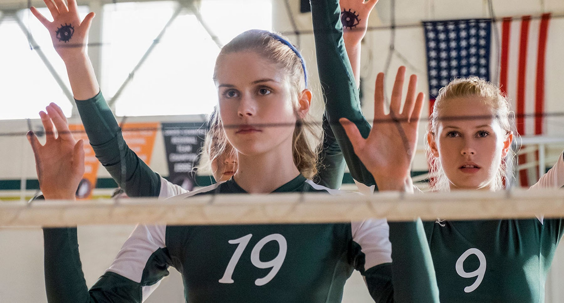 "Danika Yarosh (as Caroline Found) and Erin Moriarty (as Kelley Fliehler) near a volleyball net in the movie ""The Miracle Season"""