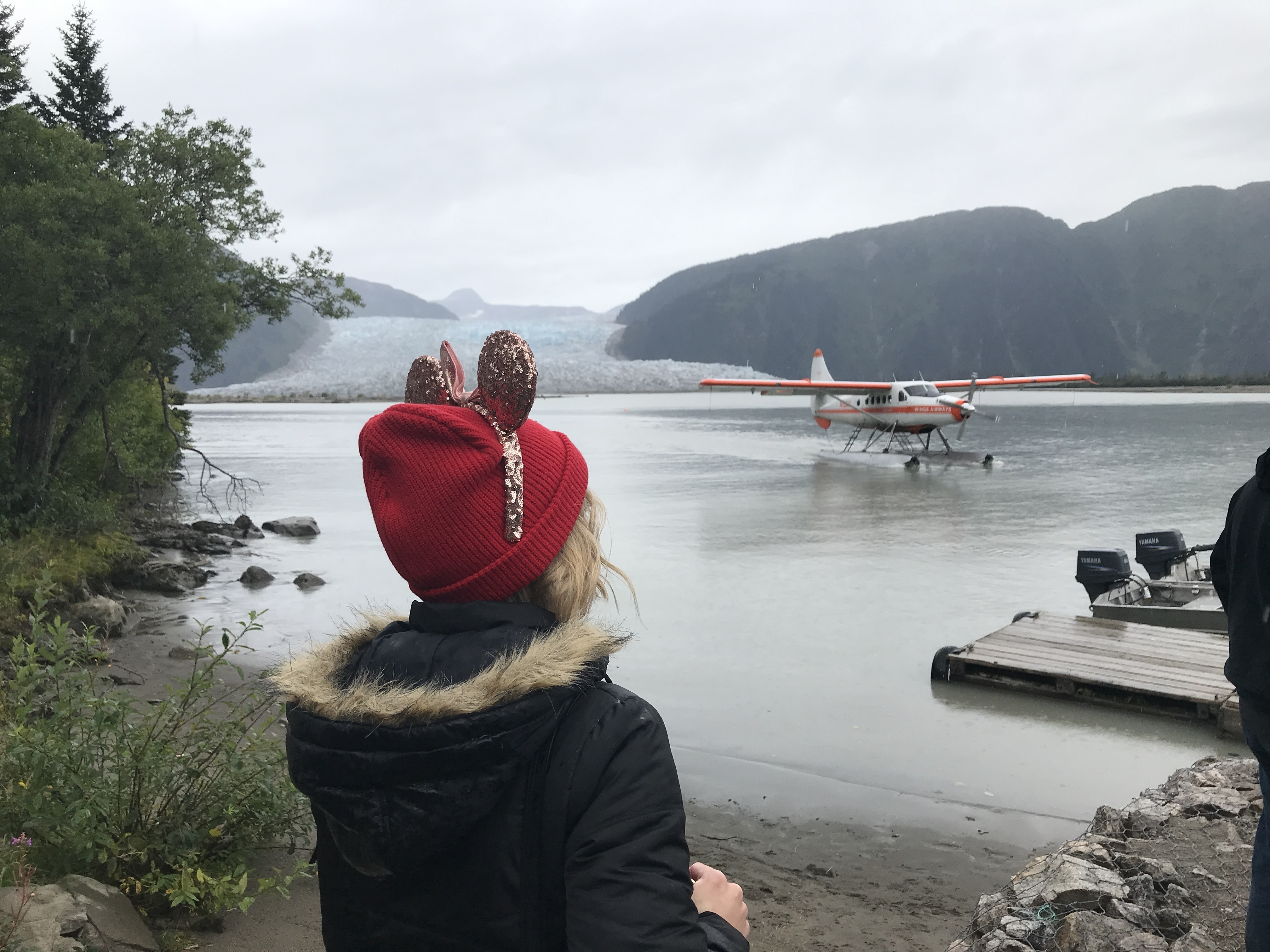 Seaplane coming in and Oh My Disney Host wearing Minnie Ears Looking out at Taku Glacier on Disney Wonder Alaska Cruise