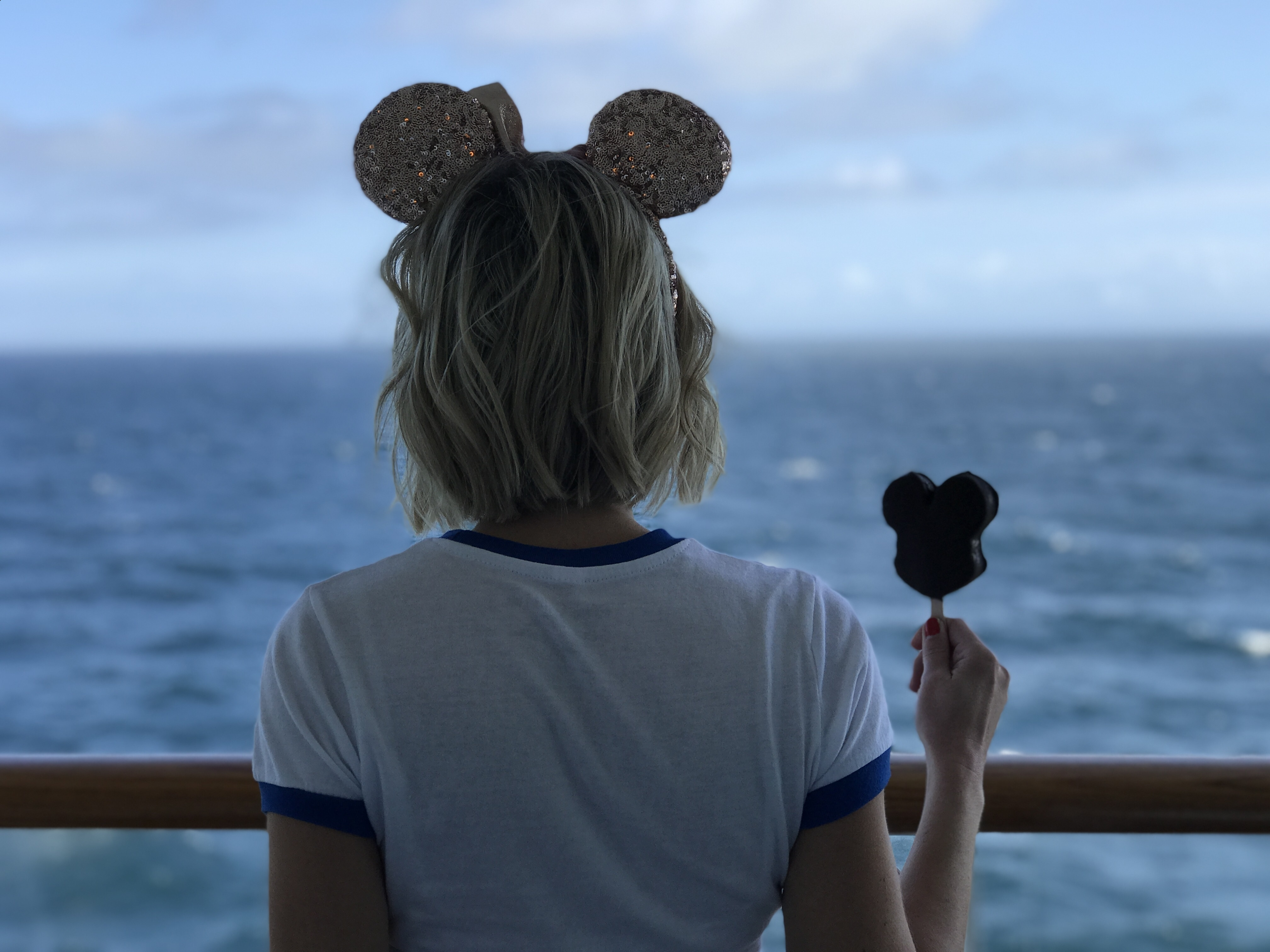 Oh My Disney Host holding Mickey Ice Cream Bar on balcony of the Disney Wonder
