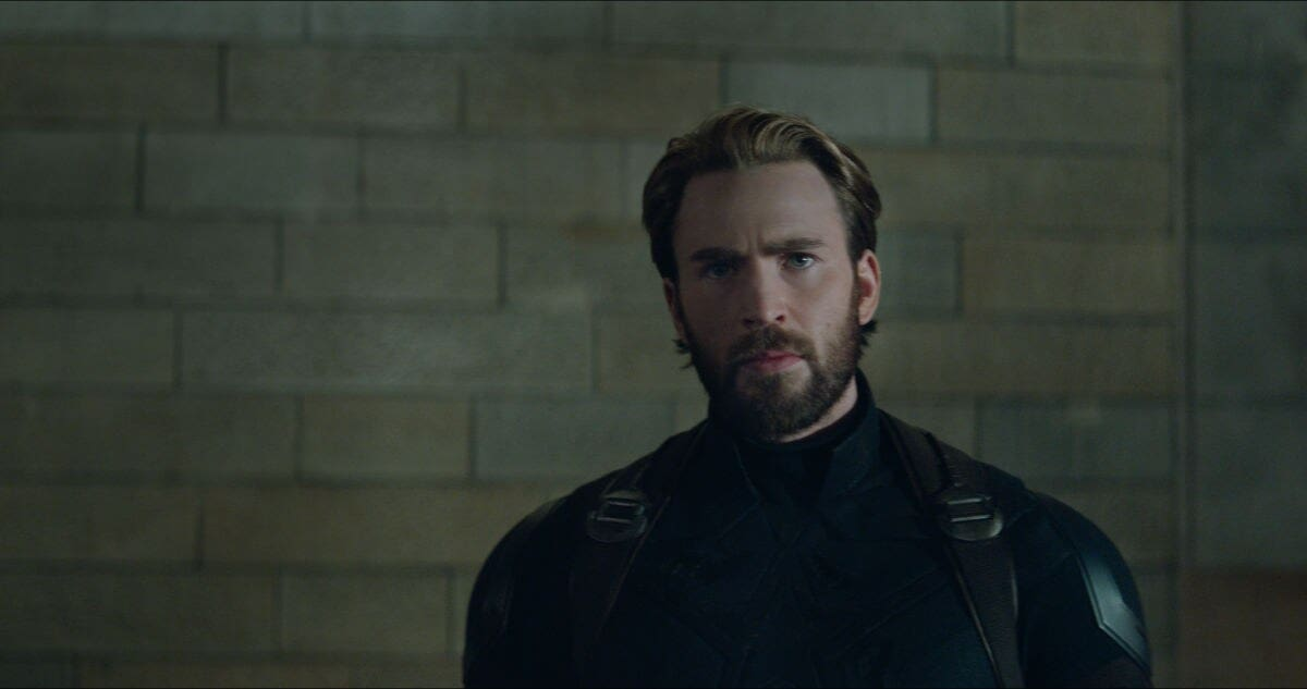 Captain America stands against a brick wall in this scene from Avengers: Infinity War.