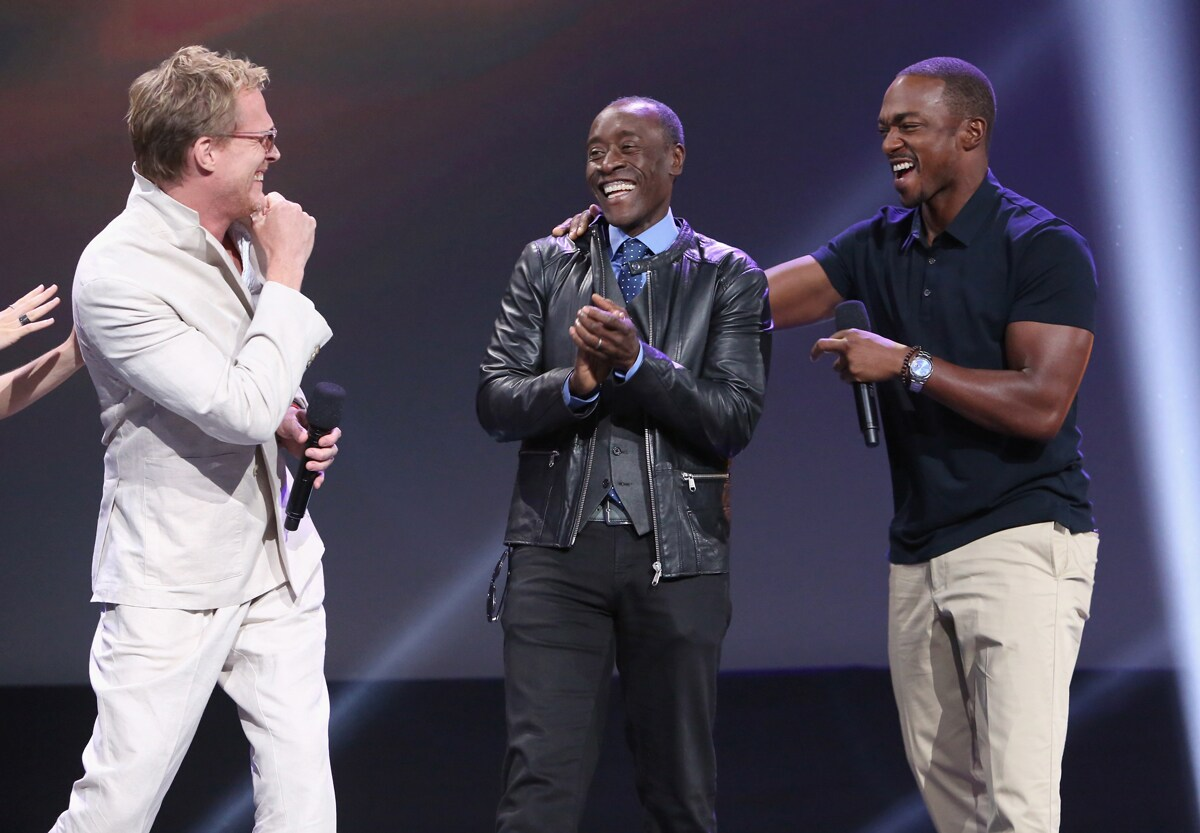 Paul Bettany, Don Cheadle and Anthony Mackie stand on a stage laughing together against a blue background.
