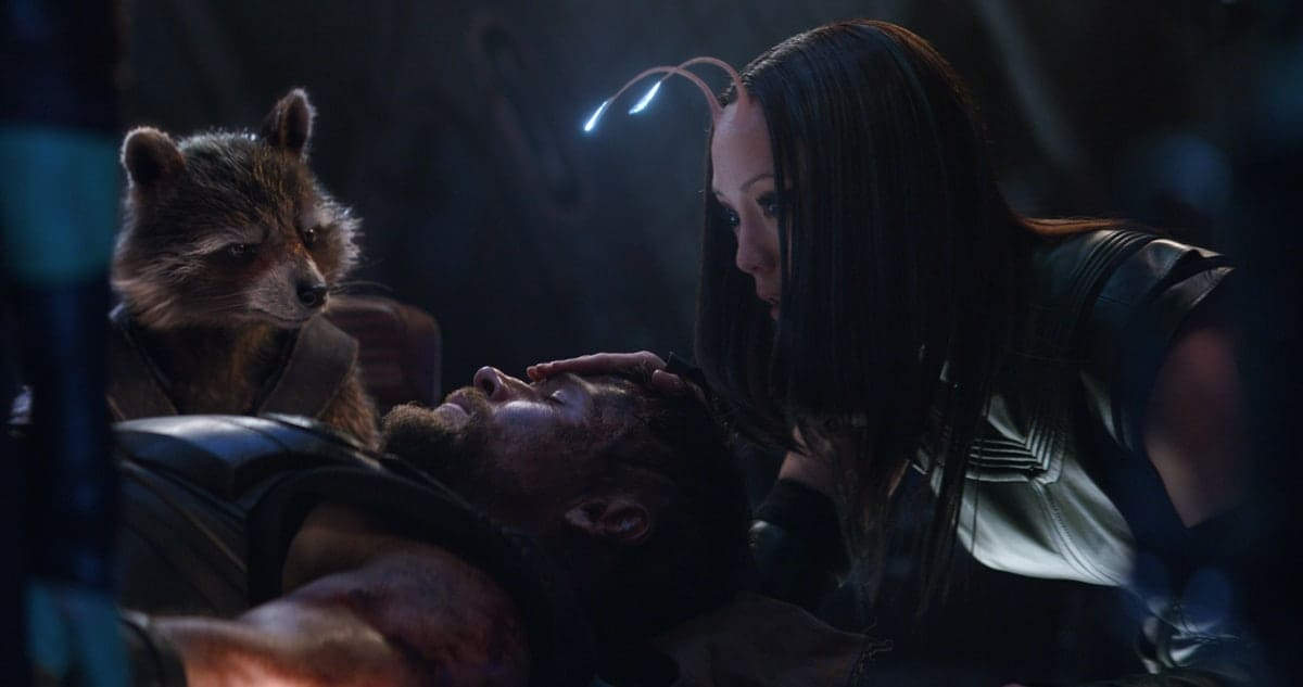 Mantis and Rocket stand over Thor in a scene from the movie Avengers: Infinity War.