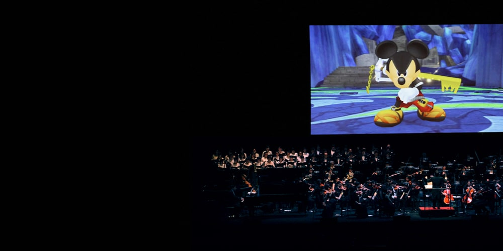 Un'orchestra suona su un palco mentre viene proiettata una scena con Topolino su un grande schermo sullo sfondo