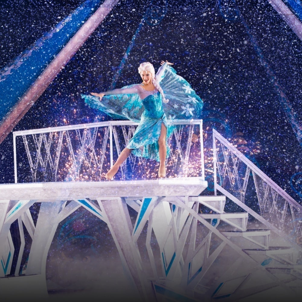Elsa on a platform with her hands raised up