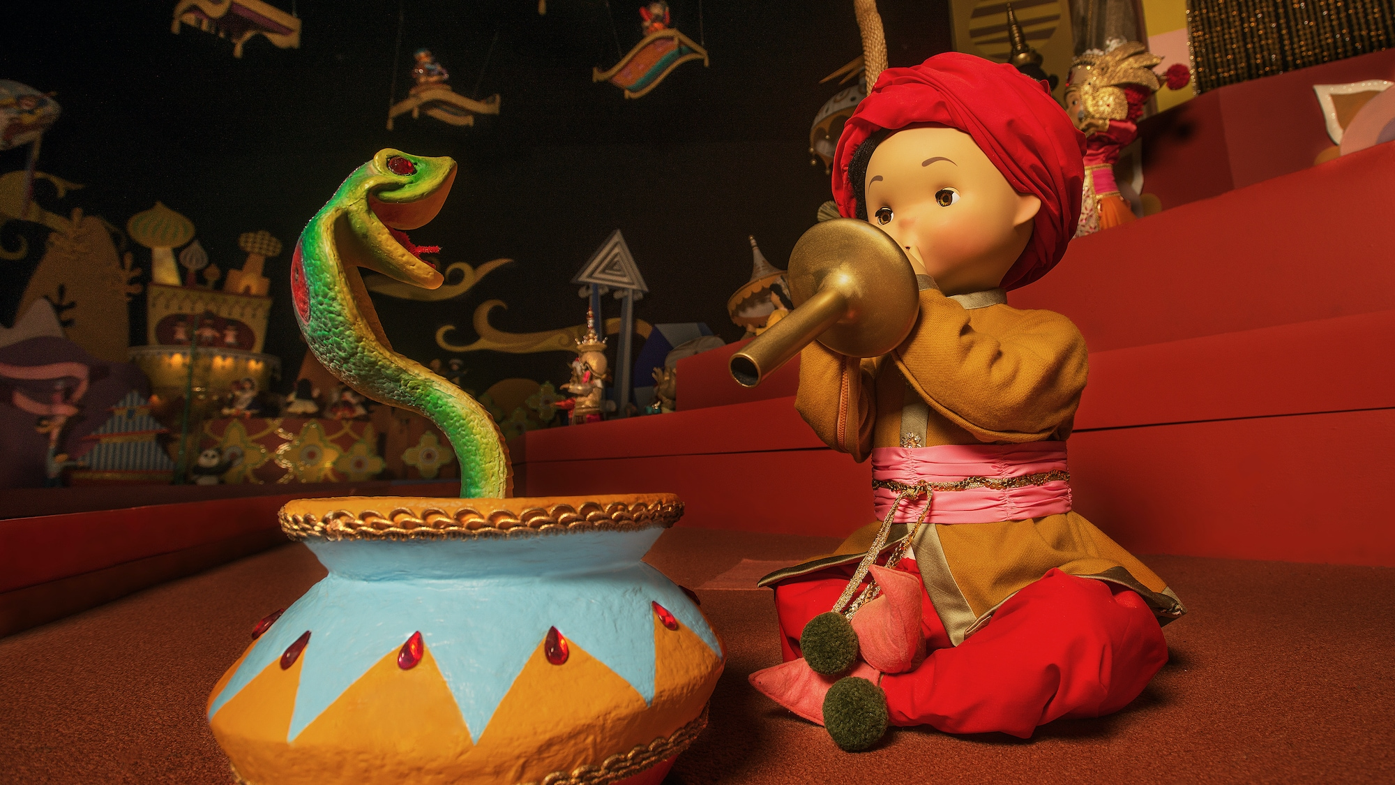 """Image of a snake charmer and snake from the """"it's a small world"""" ride."""