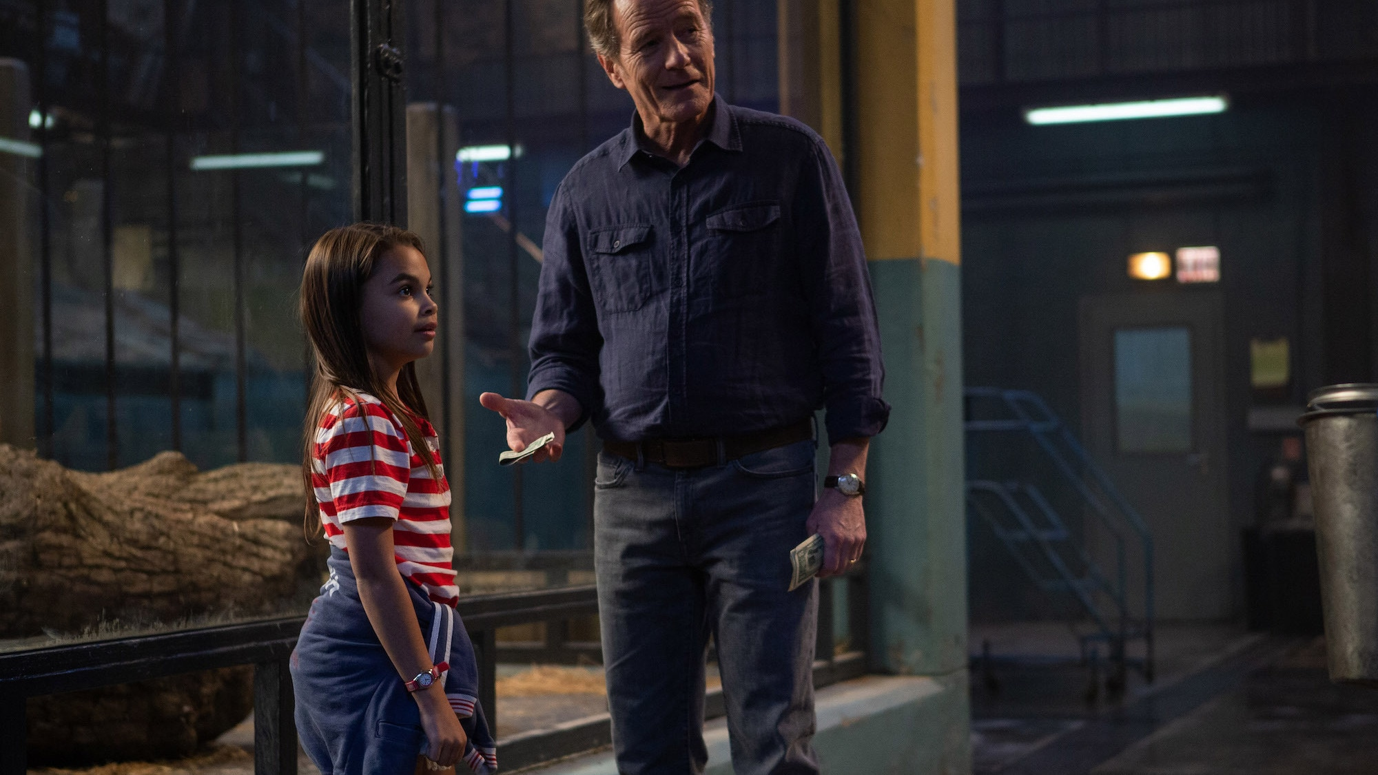 Ariana Greenblatt as Julia and Bryan Cranston as Mack in Disney's THE ONE AND ONLY IVAN, based on the award-winning book by Katherine Applegate and directed by Thea Sharrock. Photo courtesy of Disney. © 2020 Disney Enterprises, Inc. All Rights Reserved.