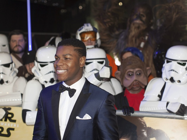 A dapper John Boyega (Finn in the film) smiles for the press at the event, overseen by Stormtroop...