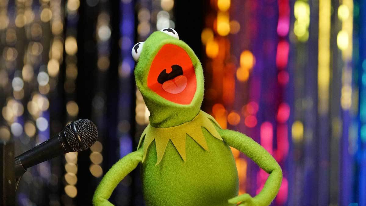 Kermit singing next to a microphone