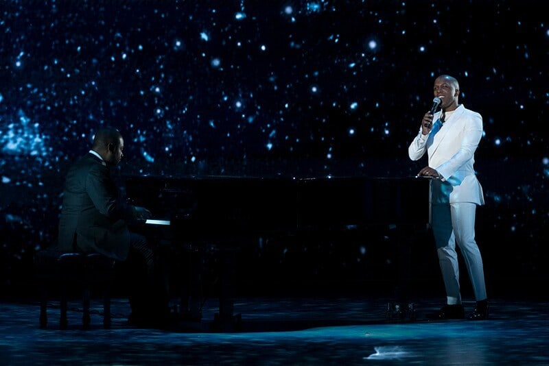 Leslie Odom Jr. Singing in white suit at a piano.
