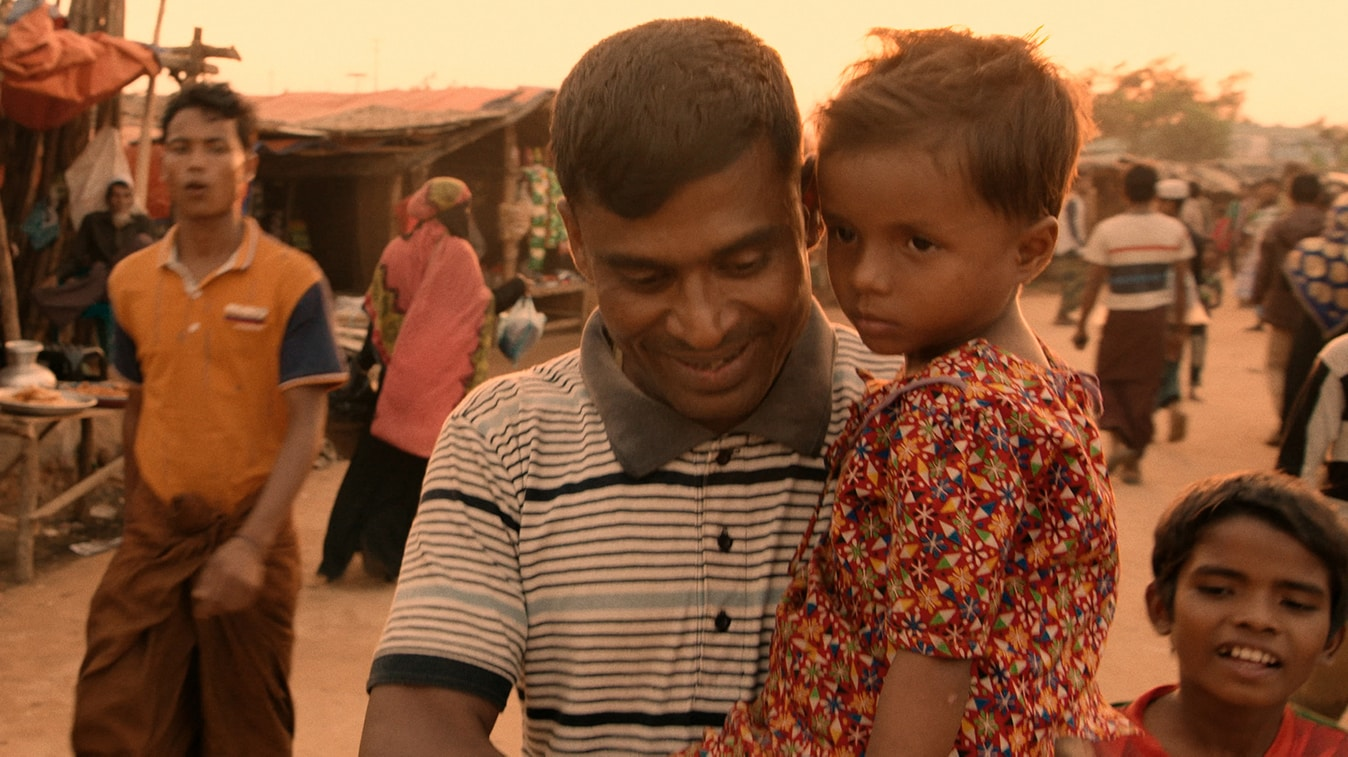 Kamal Hussein holds Dokana, a lost girl, in the Kutupalong Refugee Camp. (Photo by Nobel Media/Franklin Dow)