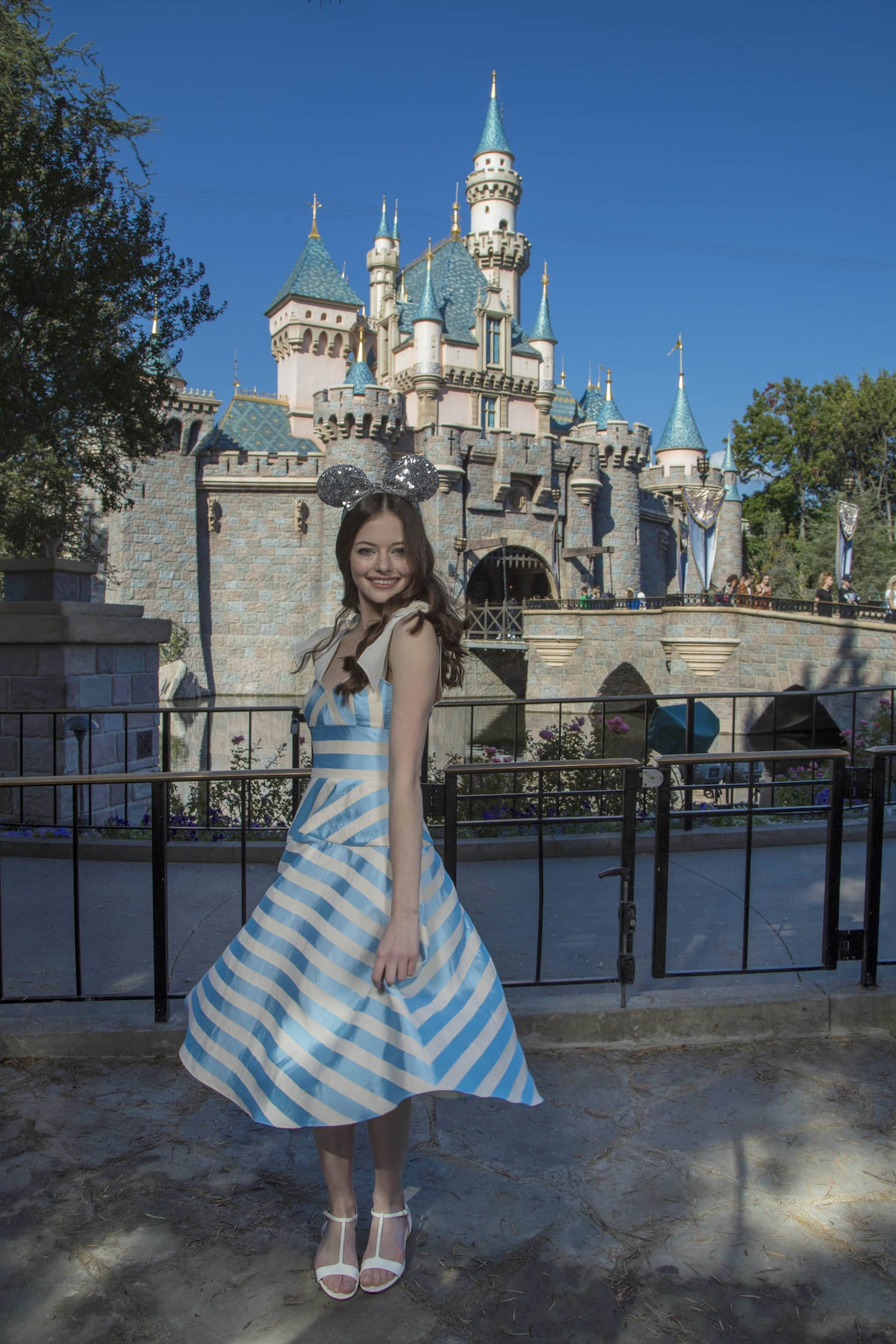 Mackenzie Foy in Blue and White striped dress posing in front of the Disneyland castle