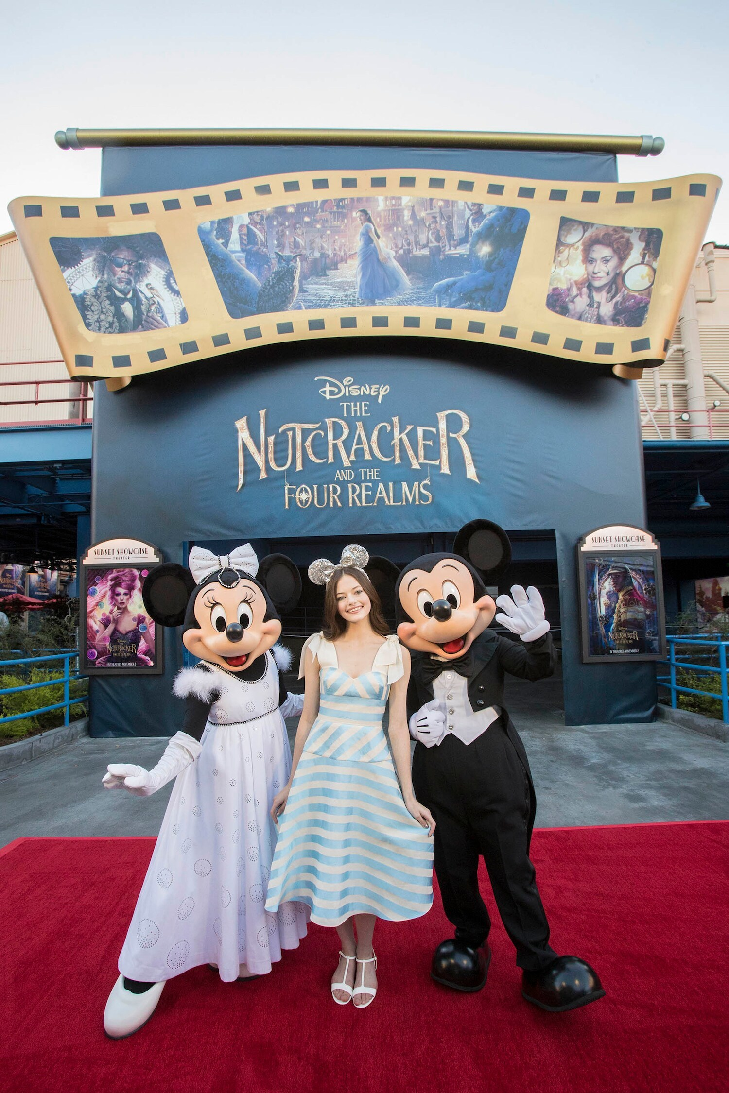 Mackenzie Foy posing with Minnie and Mickey at Disney The Nutcracker and the Four Realms