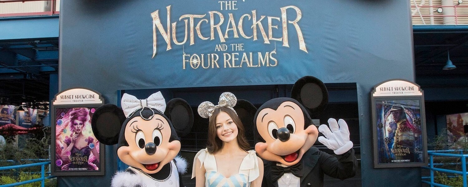 Minnie Makenzie Foy and Mickey Posing in front of display for Disney The Nutcracker and the Four Realms