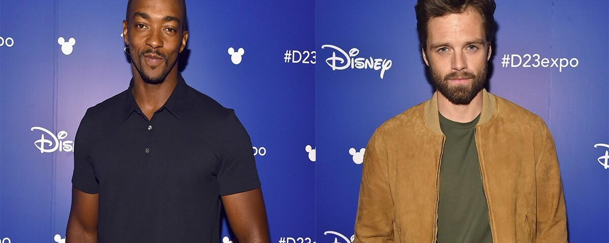Anthony Mackie and Sebastian Stan stand against a blue step and repeat at D23 Expo
