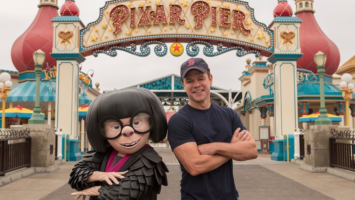 Edna Mode and Matt Damon posing in front of Pixar Pier