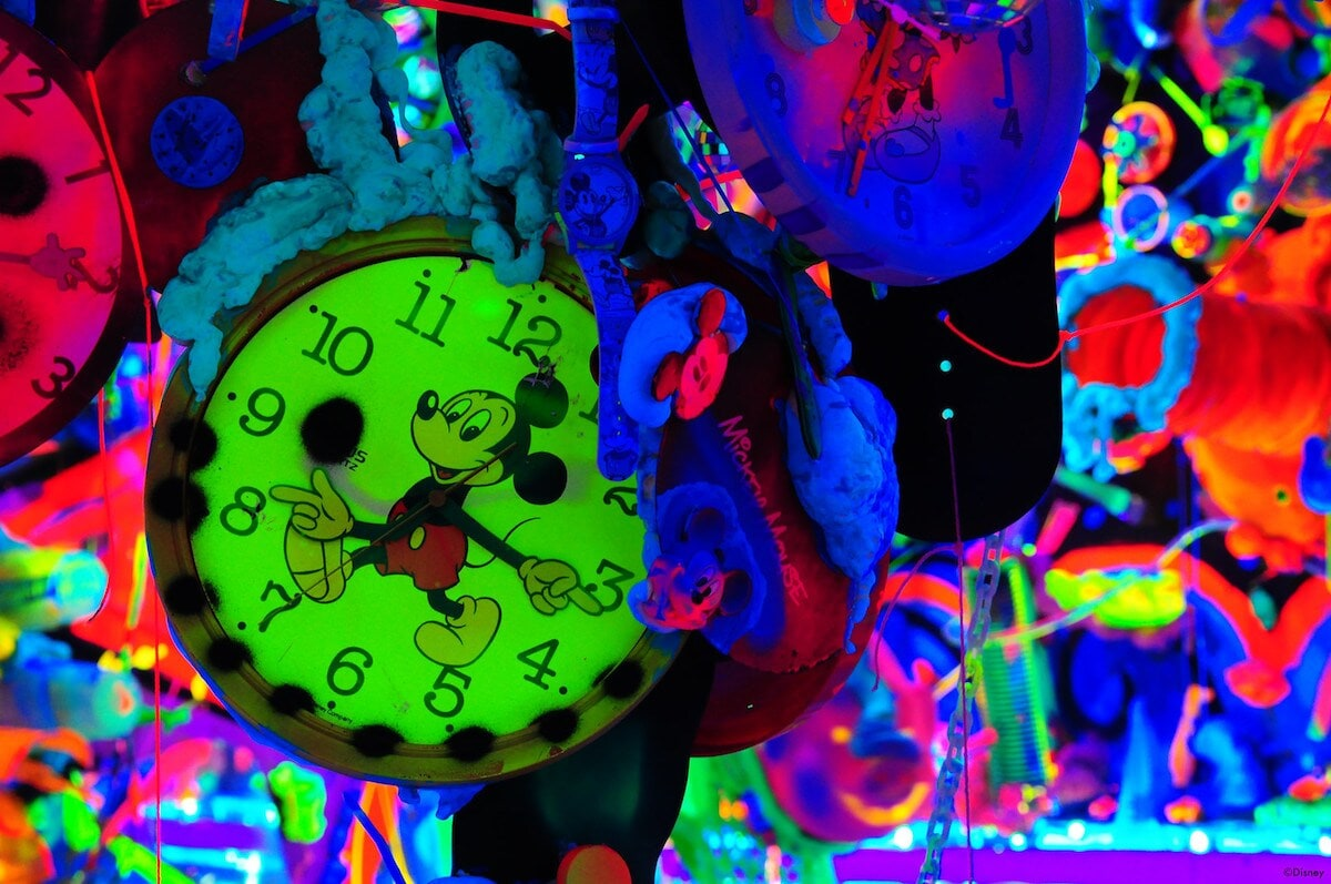 Multicolored neon Mickey Mouse art display with glowing green mickey watch