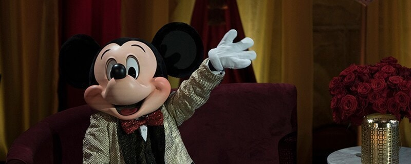 Mickey waving in shimmering gold suit jacket and shimmering red bowtie.