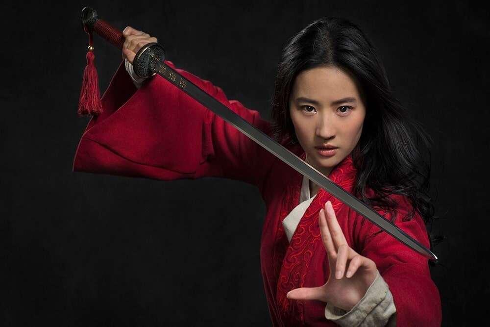 Mulan stands against a black background wearing a red Chinese robe. She is brandishing a sword.