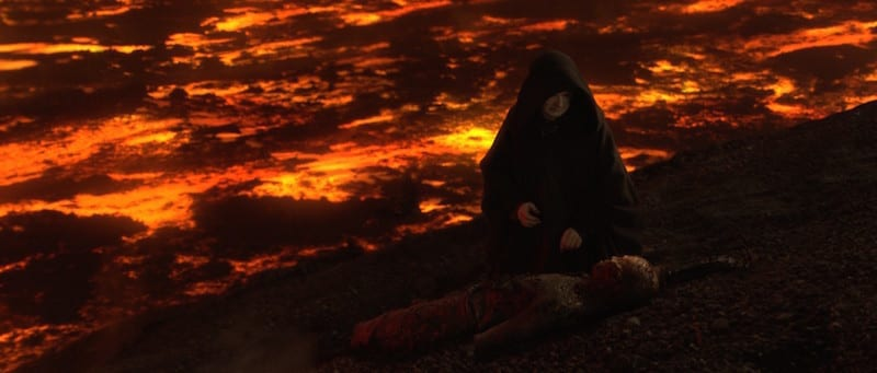 Darth Sidious kneeling over a defeated Anakin Skywalker on Mustafar