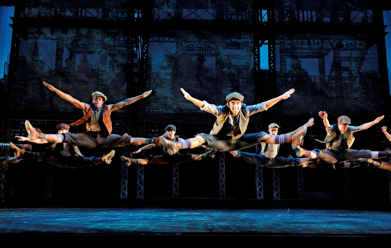 The cast of Newsies performing a dance on stage