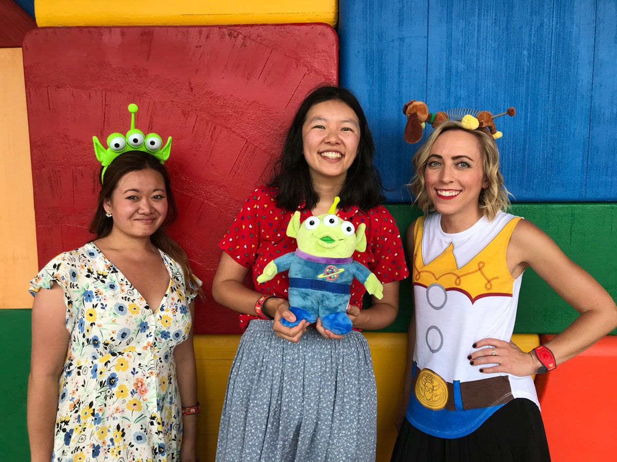 Oh My Disney Correspondents Jenny Tran, Kelly Lin, and Michelle Lema in front of a toy block wall in Toy Story Land in Walt Disney World