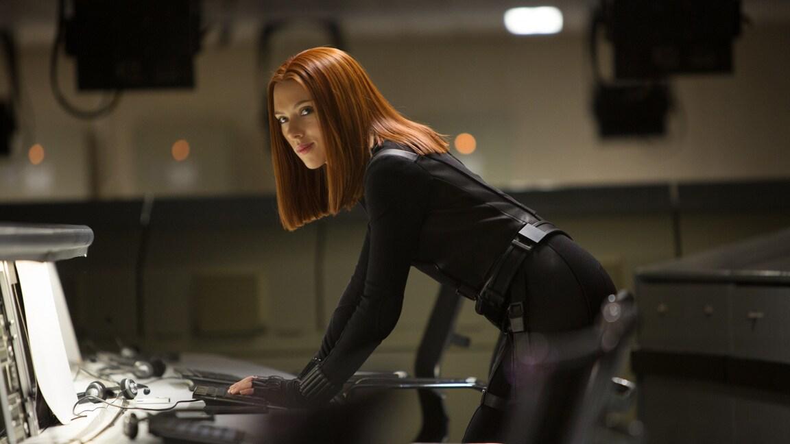Actor Scarlett Johansson (Natasha Romanoff/Black Widow) standing in front of a desk in Captain America: The Winter Soldier.