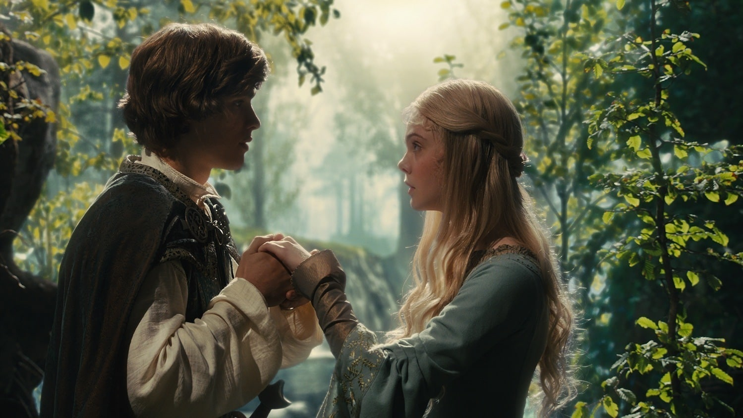"""Elle Fanning as Aurora and Brenton Thwaites as Prince Phillip holding hands surrounded by trees in """"Maleficent"""""""