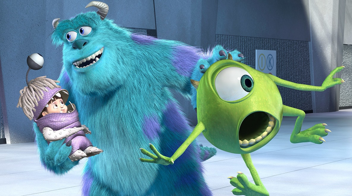 Shocked Billy Crystal as Mike Wazowski and smiling John Goodman as Sully holding a costumed Boo in Monsters, Inc.