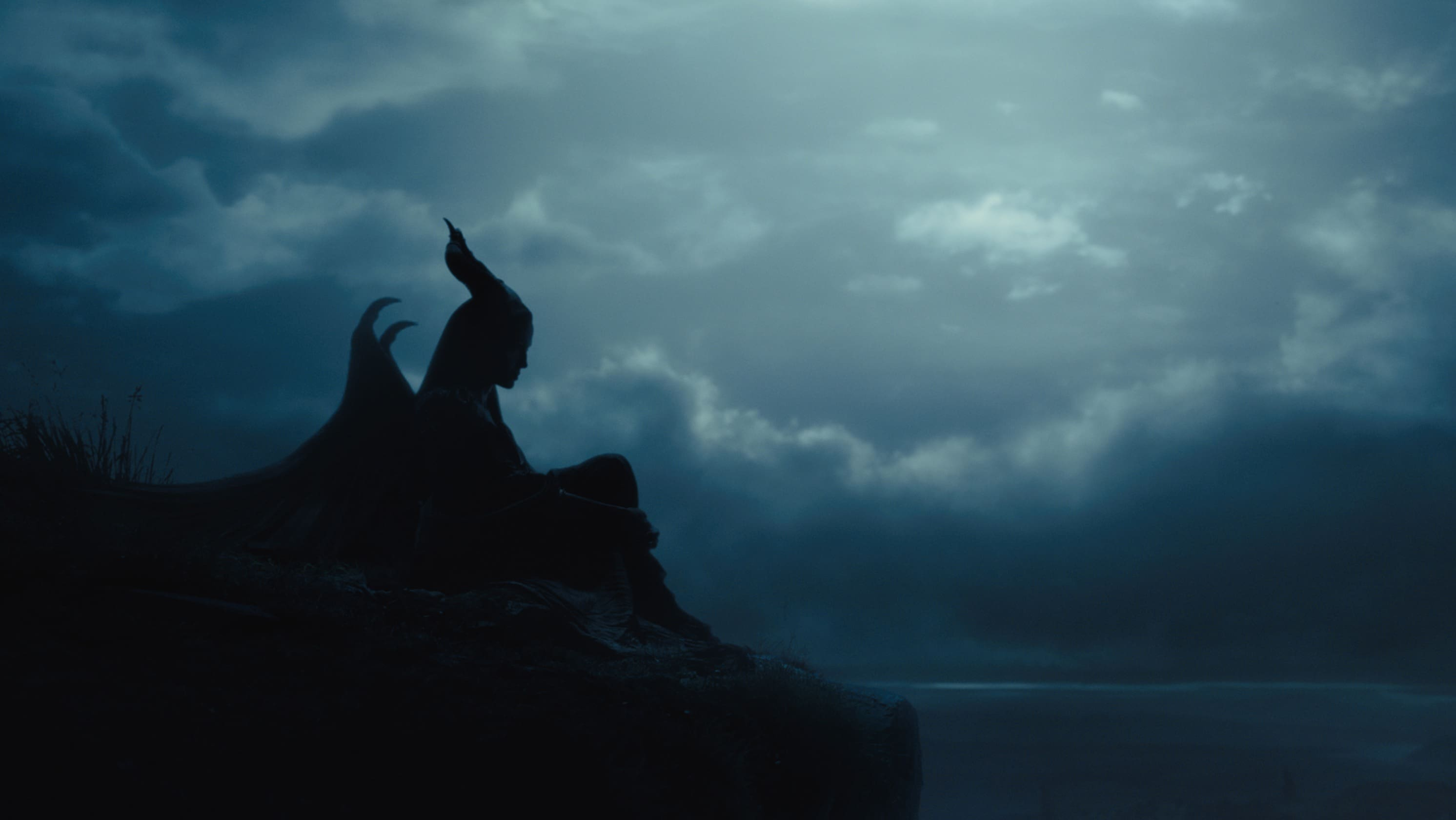 """The silhouette of Angelina Jolie as Maleficent sitting on a rock in the movie """"Maleficent"""""""