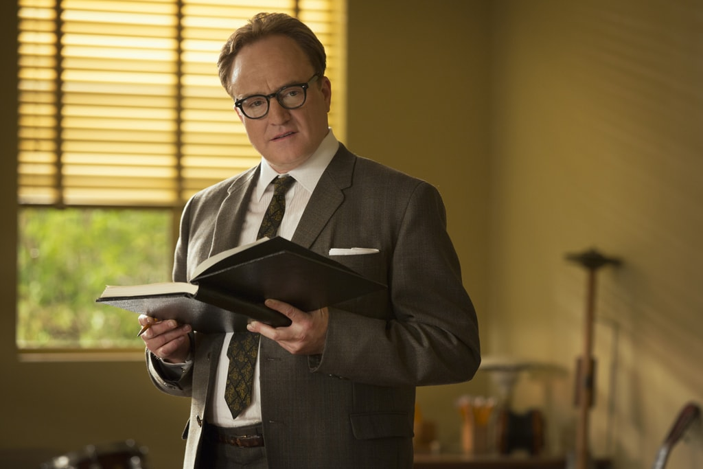 """Actor Bradley Whitford as Don DaGradi standing with an open book in the movie """"Saving Mr. Banks""""."""