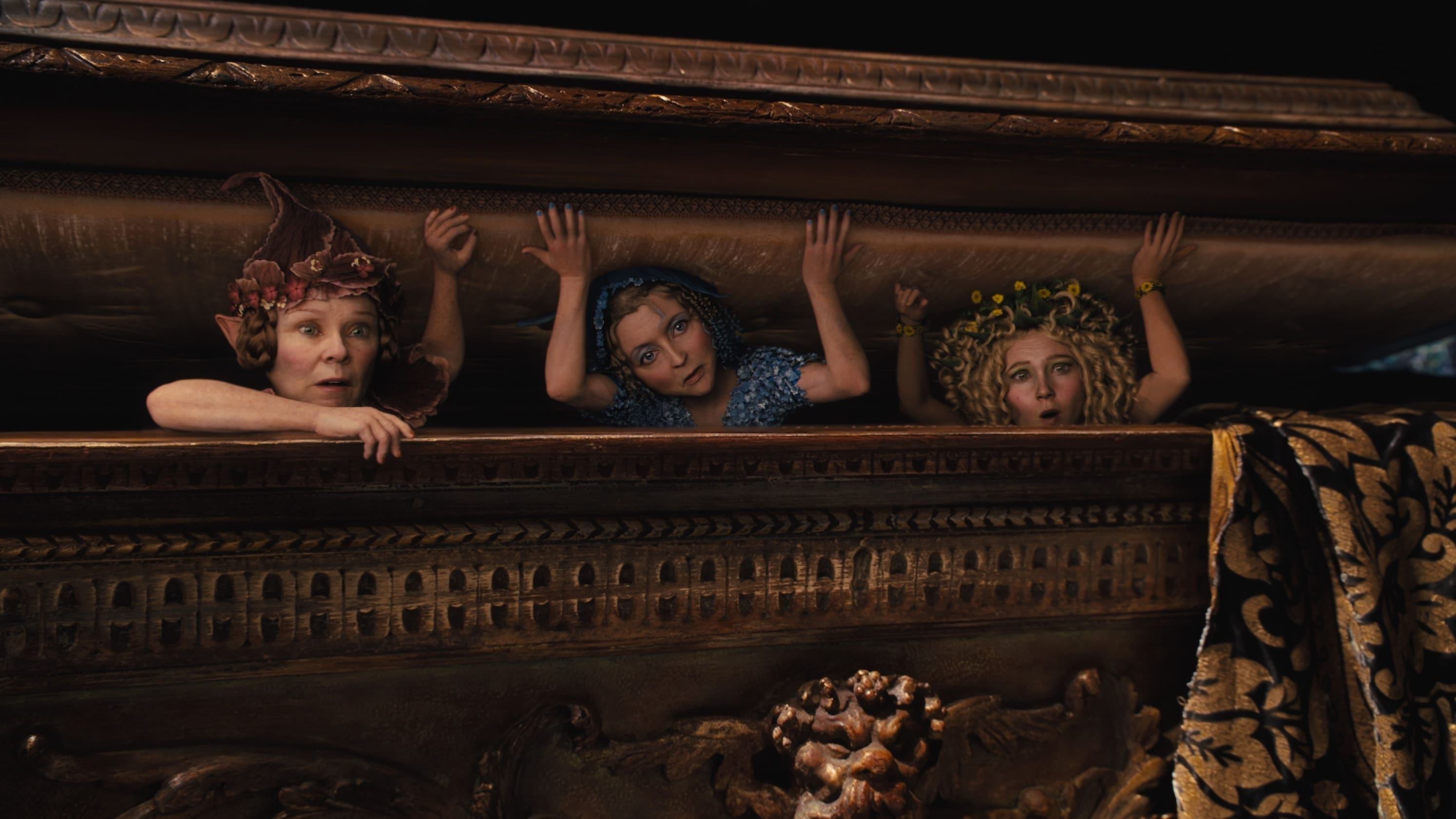 """The three flower pixies, Knotgrass (played by Imelda Stauton), Flittle (played by Lesley Manville), and Thistlewhit (played by Juno Temple) peeking out of a box in the movie """"Maleficent"""""""