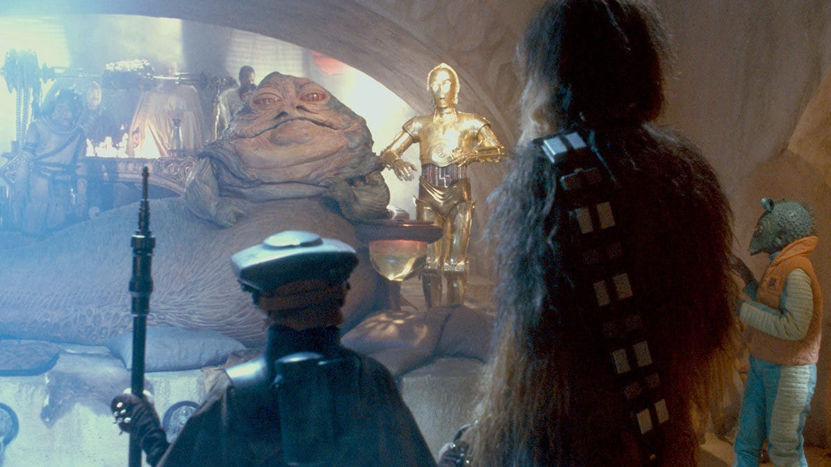 Jabba the Hutt addressing Chewbacca and a disguised Leia Organa