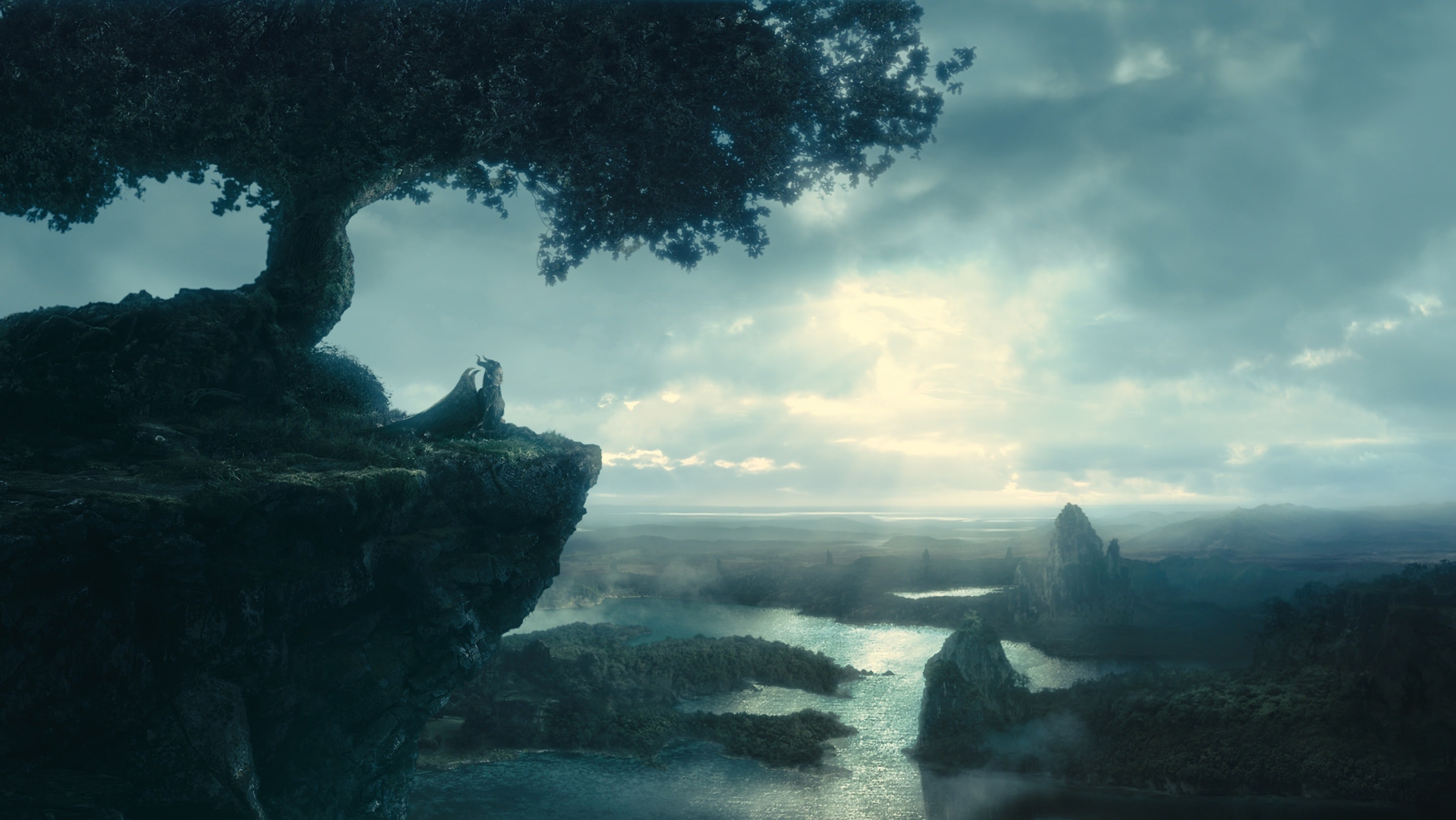 """Angelina Jolie as Maleficent sitting under a tree overlooking the river or bay in the movie """"Maleficent"""""""