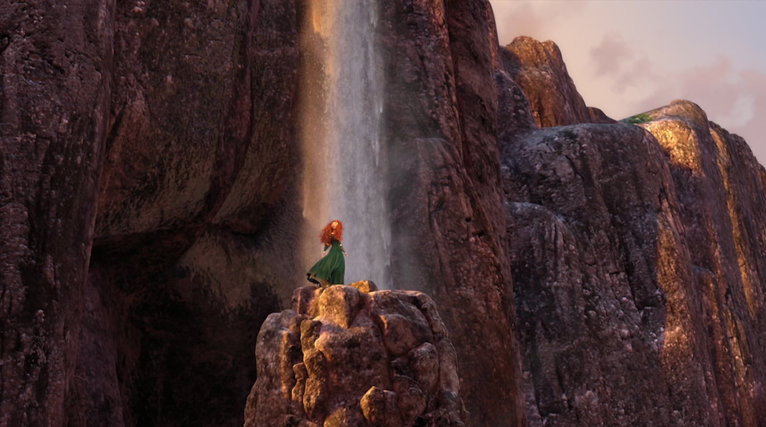 Merida, voiced by Kelly Macdonald, standing on a rock in front of the Fire Falls in the movie Brave