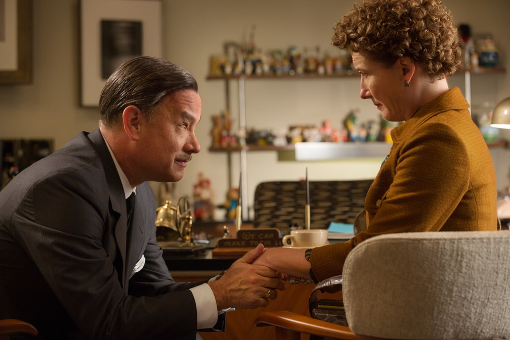 """Actor Tom Hanks (as Walt Disney) holds the hand of Emma Thompson (as P.L. Travers) in the movie """"Saving Mr. Banks""""."""
