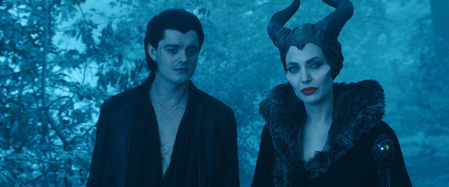 """Angelina Jolie as Maleficent and Sam Riley as Diaval standing in the forest in the movie """"Maleficent"""""""