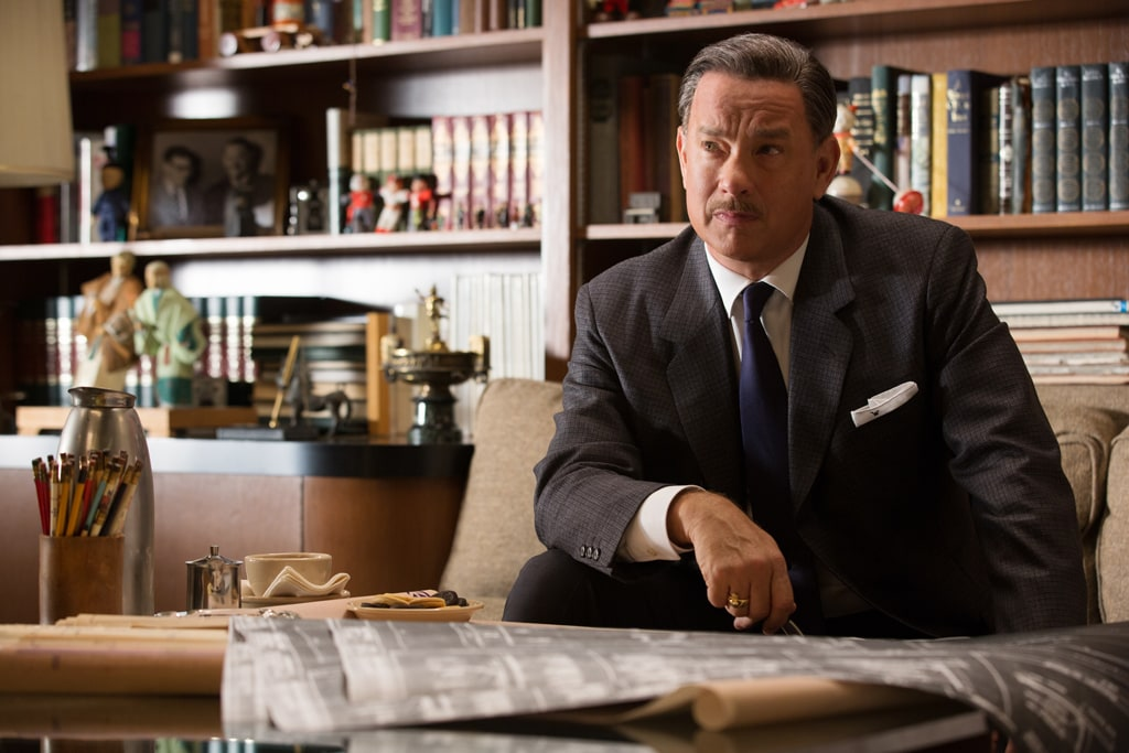 """Actor Tom Hanks as Walt Disney sitting on a couch in the movie """"Saving Mr. Banks""""."""