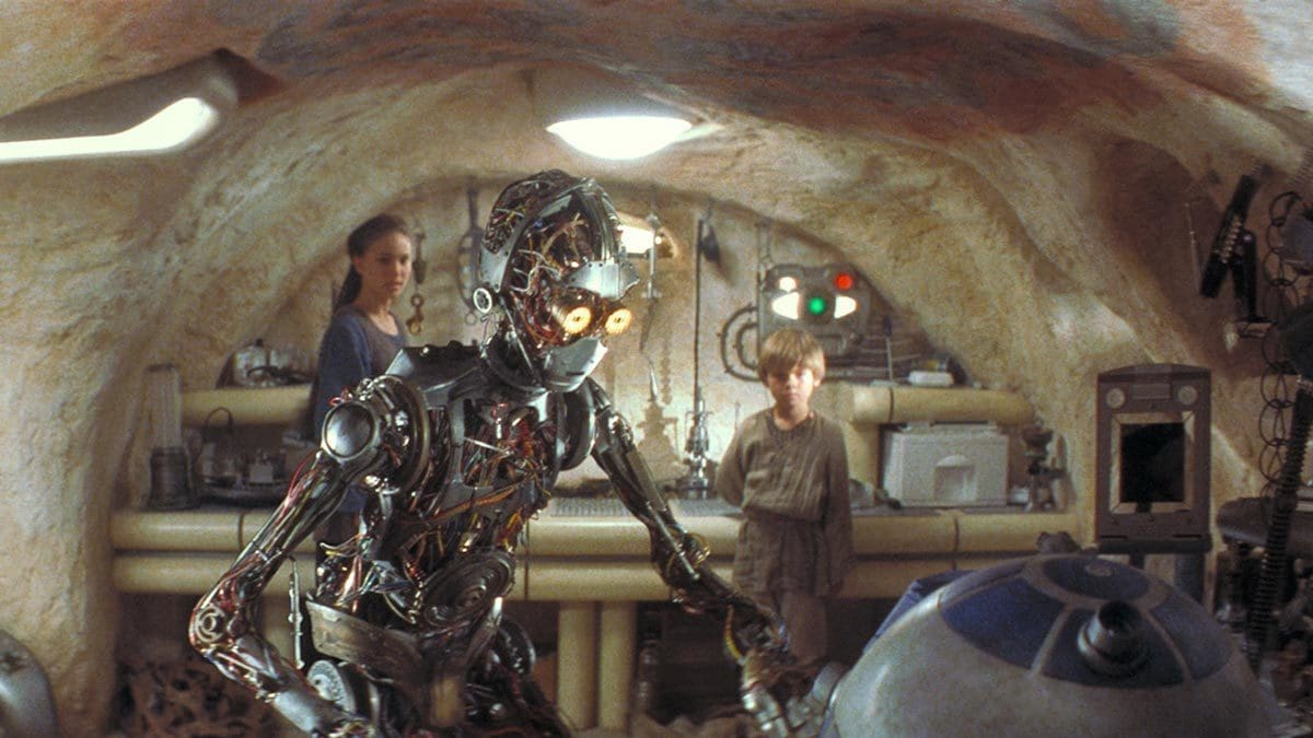 C-3PO greeting R2-D2 as Anakin and Padme observe