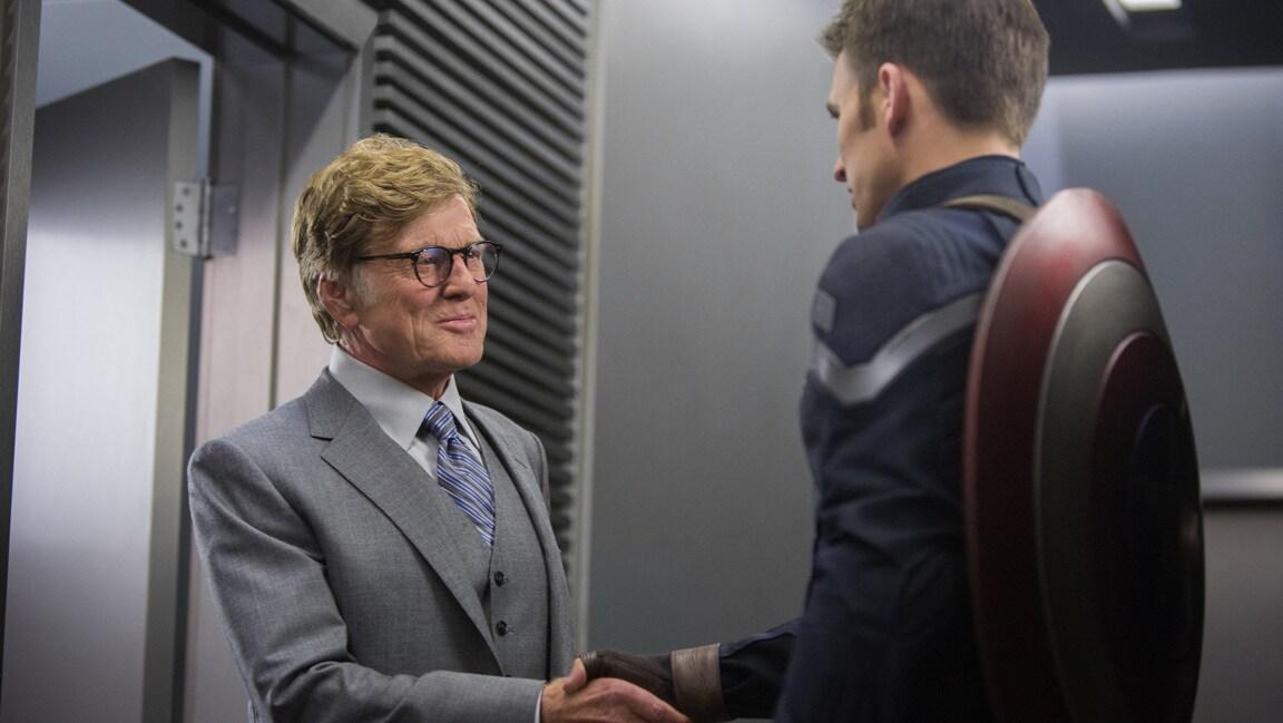 Actors Robert Redford (Alexander Pierce) and Chris Evans (Steve Rogers/Captain America) shake hands in Captain America: The Winter Soldier.