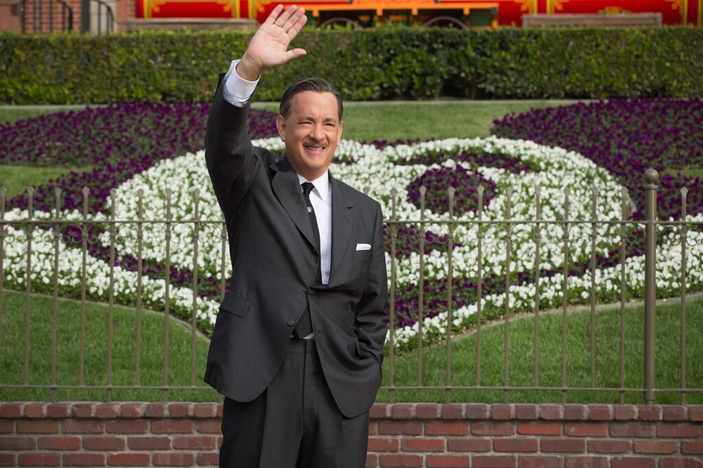 "Actor Tom Hanks as Walt Disney standing and waving in front of Disneyland in the movie ""Saving Mr. Banks""."