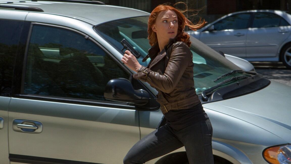 Actor Scarlett Johansson (Natasha Romanoff/Black Widow) running past a car in Captain America: The Winter Soldier.